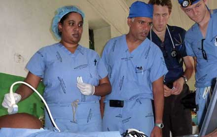On the 2010 trip to Haiti, Dr. Srinivasan and Dr. Master perform an ultrasound evaluation of an abdominal mass while teaching medical students Lee Hugar and Pete Creighton the diagnostic technique.