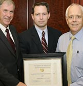 Dr. Andrew Adams receiving Woodruff Independence Award from Dr. Caugman and Dr. Stephens